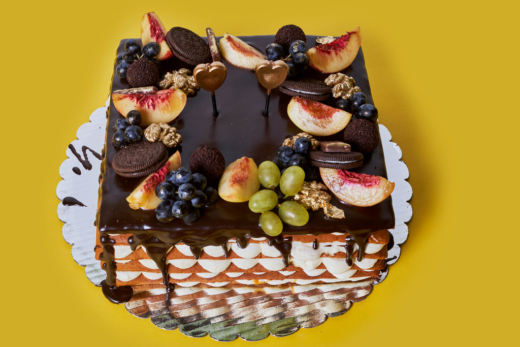 Sweet homemade chocolate cake with biscuit, grapes and peaches