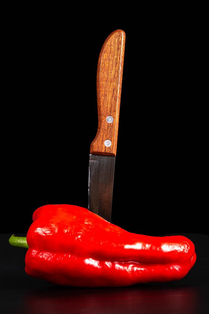 Sweet pepper with a knife on a black background