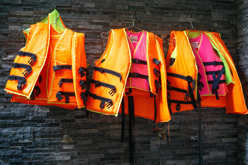 Swim Life Vests in different Colors for Adults and Children on Hangers hanging on a Wall next to a Swimming Pool in a Hotel
