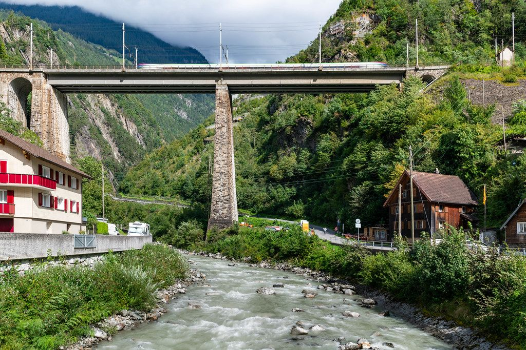 Swiss train speeding on an old tall brick bridge