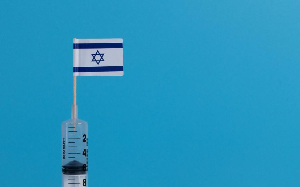 Syringe with flag of Israel on blue background