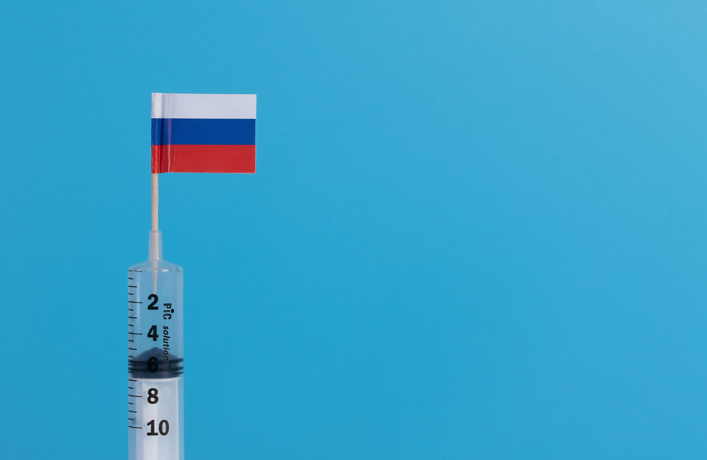 Syringe with flag of Russia on blue background