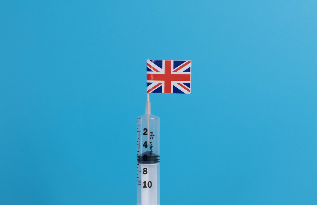 Syringe with flag of United Kingdom on blue background