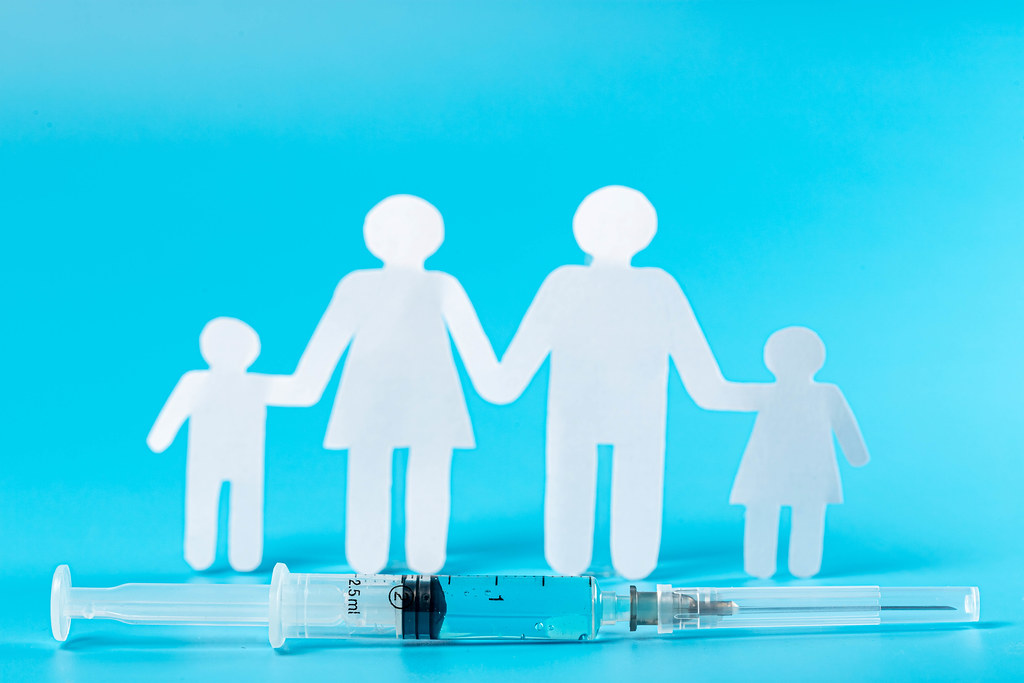 Syringe with vaccine near silhouette of family on blue background