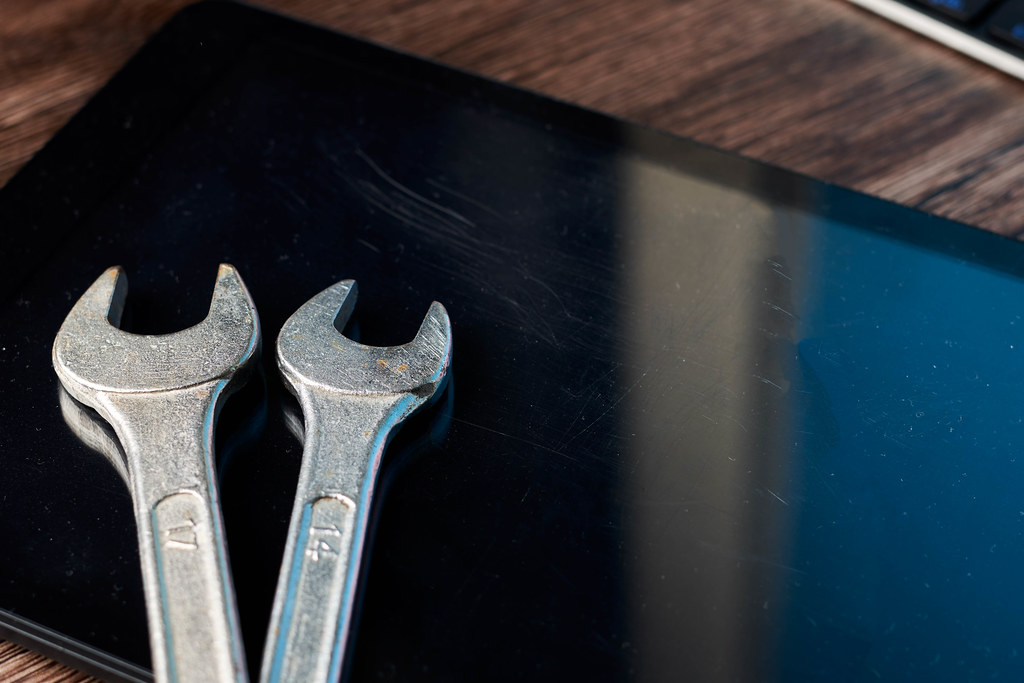 Tablet computer and wrench on wood background