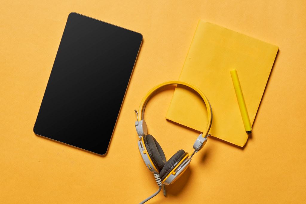Tablet with a blank screen, yellow headphones and notepad on yellow background