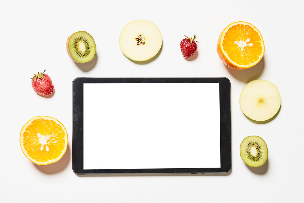 Tablet with empty white screen and various fruits slices around it