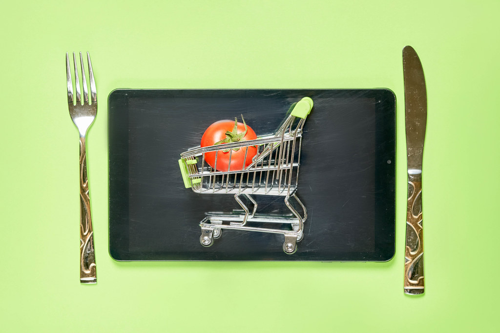 Tablet with shopping cart, spoon and fork on green