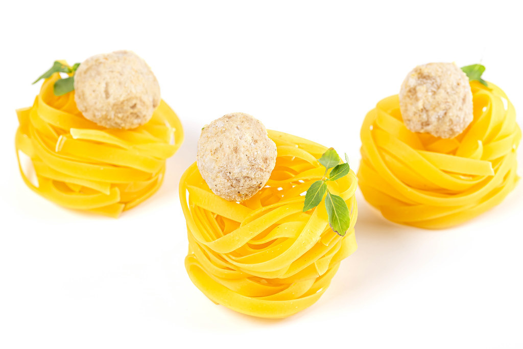 Tagliatelle with raw meatballs placed on a white background