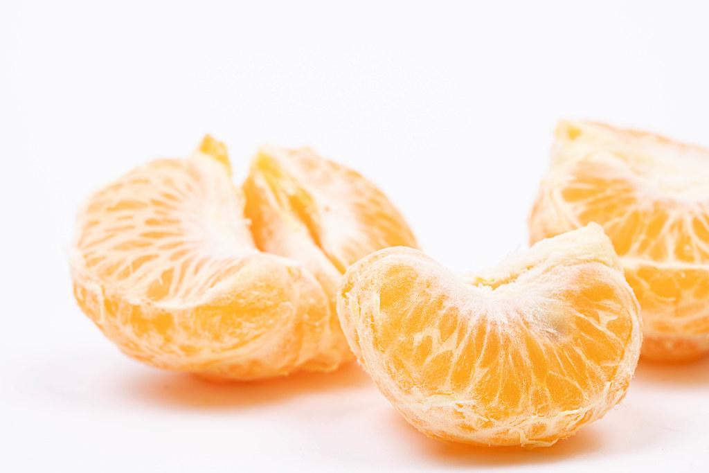 Tangerine slices above white background