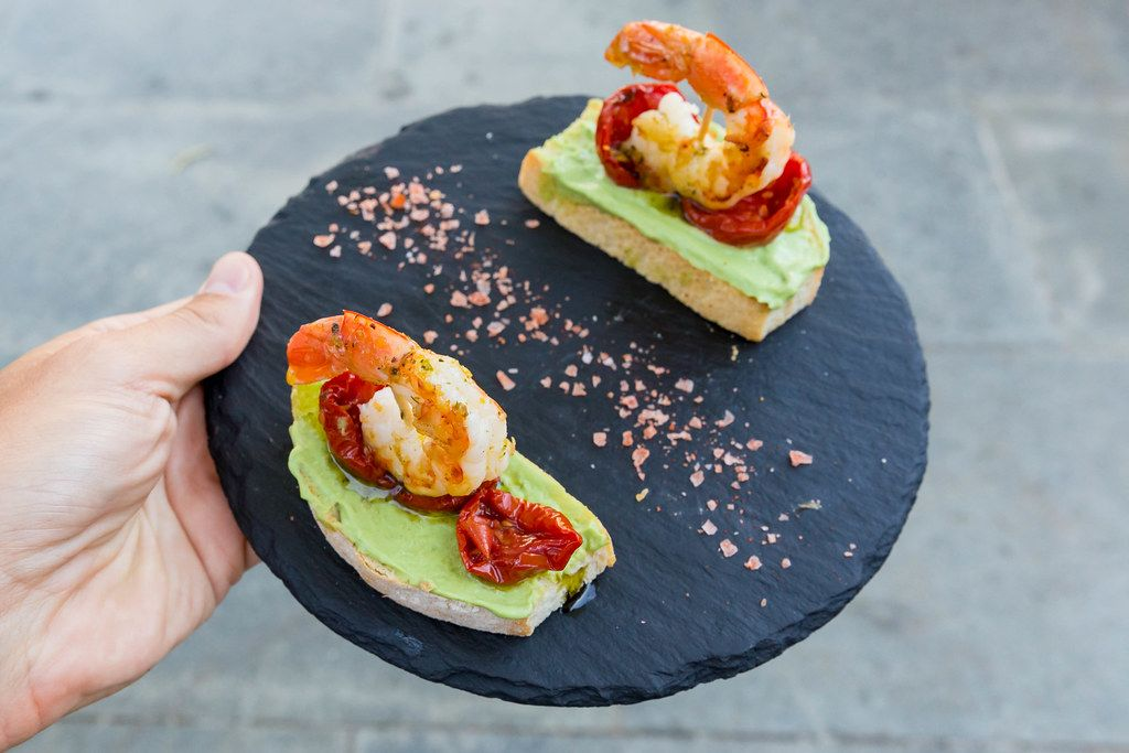 Tapas at Q11, Pollença: toasted bread, king prawns, dried tomatoes, avocado cream on a round board