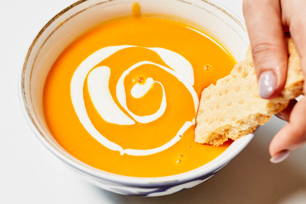 Tasting delicious creamy soup with a bread