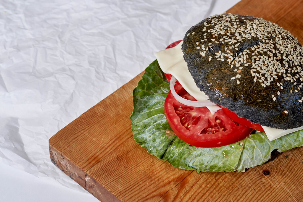 Tasty black burger with chicken meat, cheese and tomato slices on the cutting background