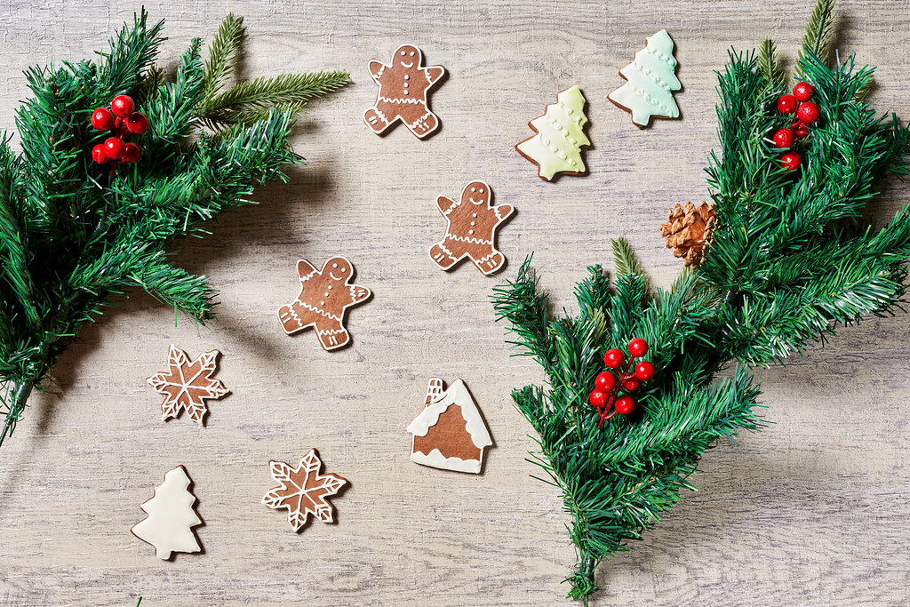 Tasty Christmas cookies and decorative pine tree branches on wood