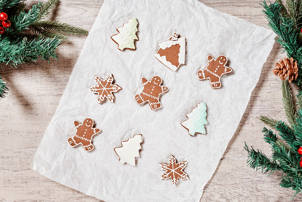 Tasty Christmas cookies and decorative pine tree branches on wooden background