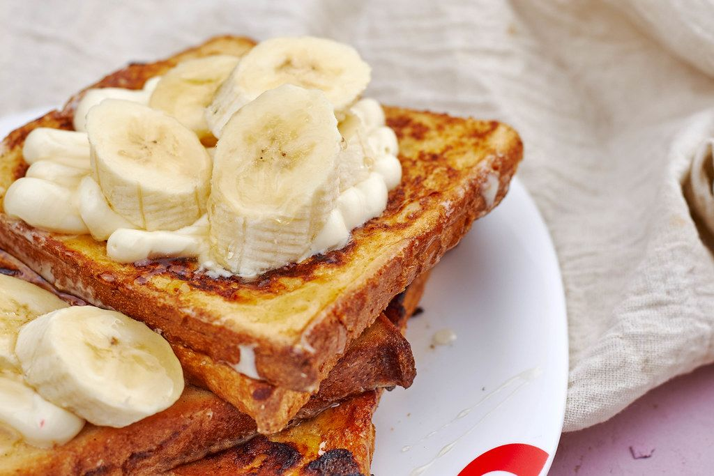 Tasty snack - Summer fruit bruschetta. Fried toasts with delicious cream and banana slices