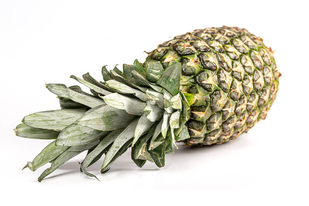 Tasty whole pineapple with leaves on white background
