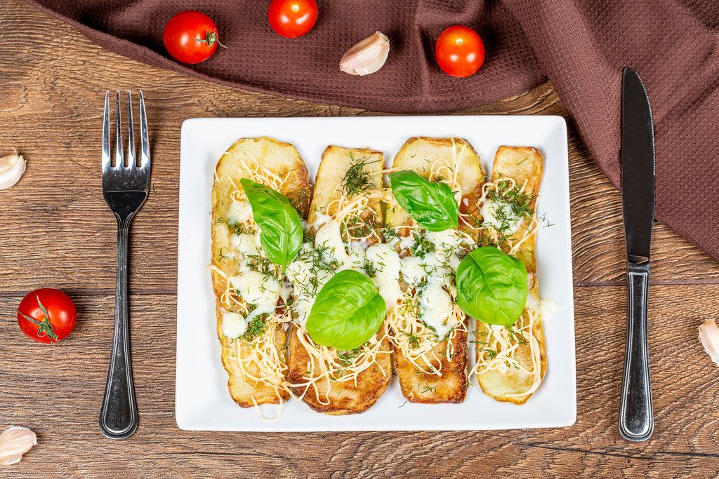 Tasty zucchini with cheese and herbs on a wooden background with knife and fork, top view