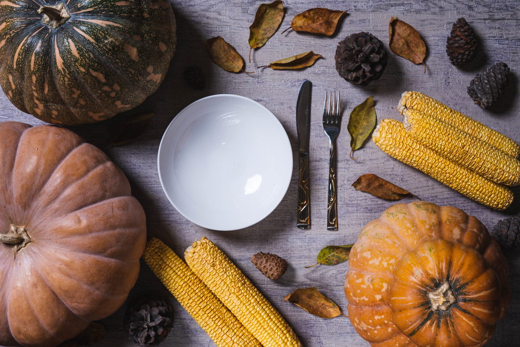 Thanksgiving background with freshly harvested pumpkins and corns