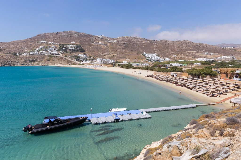 The beach of Kalo Livadi on the Greek island Mykonos with a small pier and black motor boat