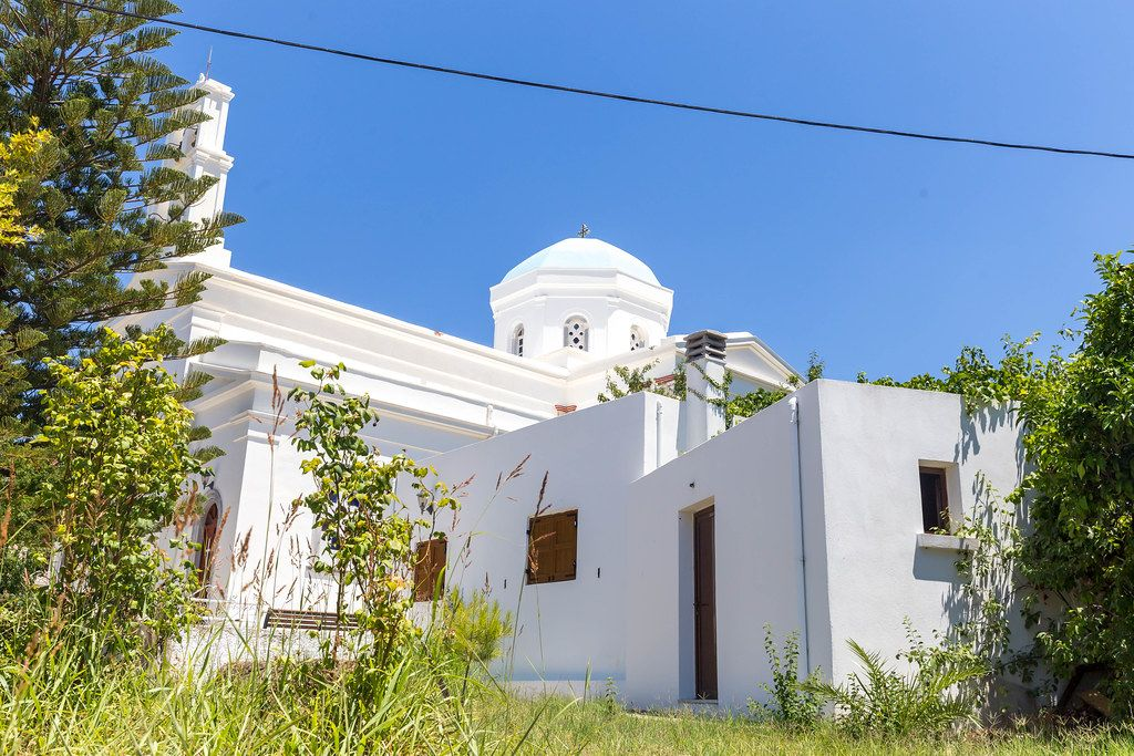 The blue dome of the white church of Panagia Protothronos against the blue sky in Halki, Naxos