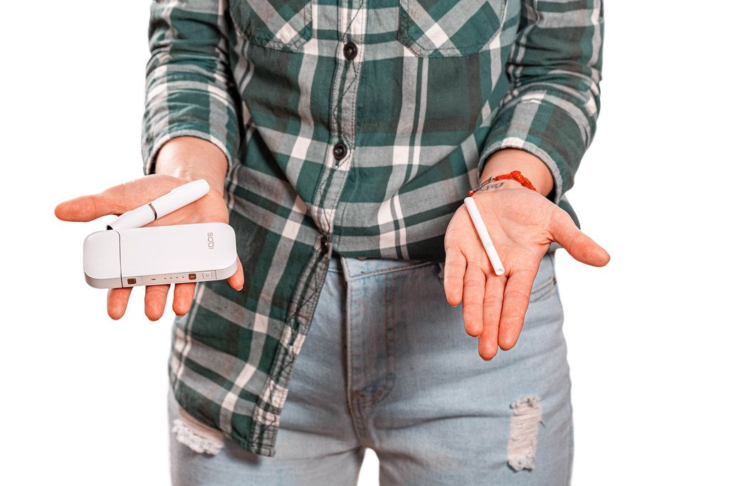 The concept of bad habits. A woman holds a cigarette in one hand and IQOS in the other