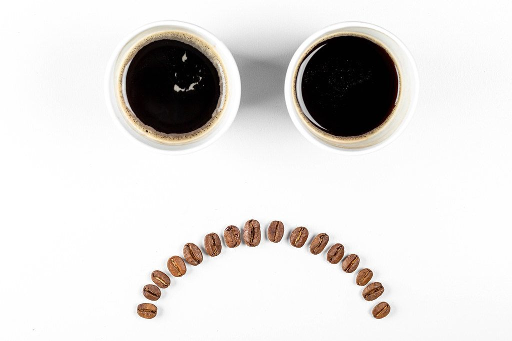 The concept of bad mood, failure. Sad emoticon of coffee and coffee beans