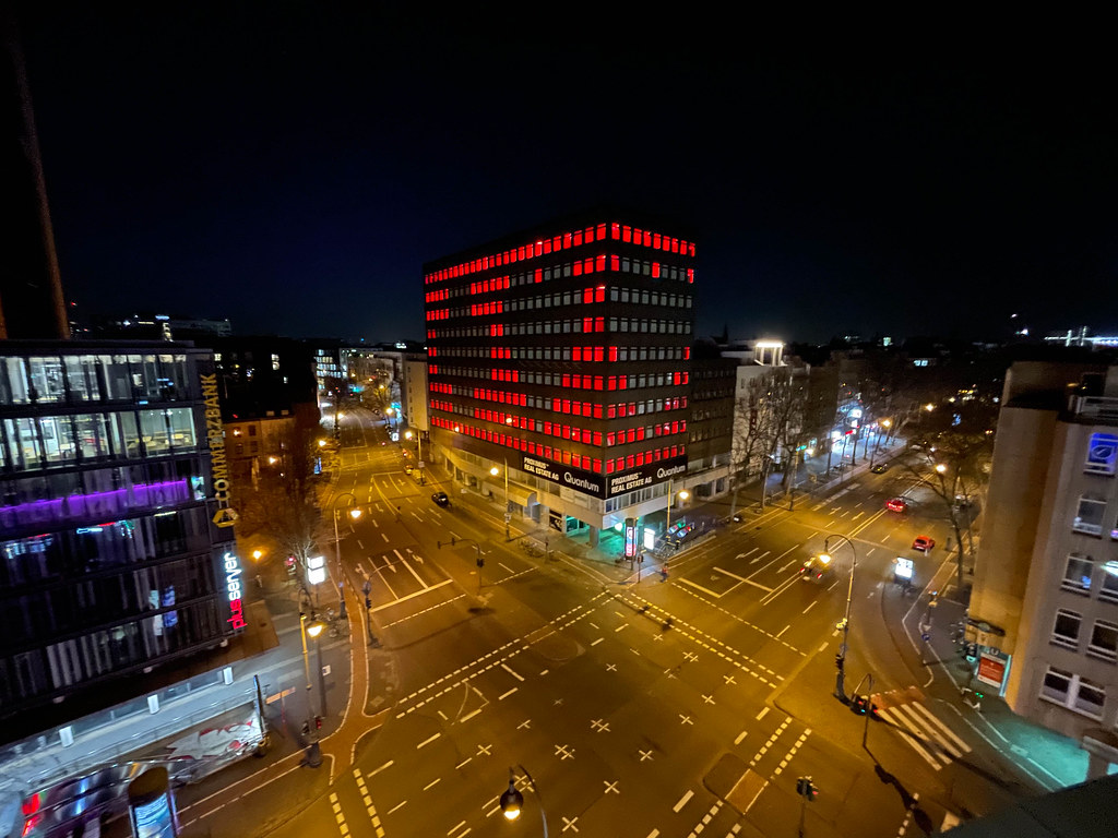 The empty building at Friesenplatz in Cologne lit by temporary installation with heart and cross by studio polylog