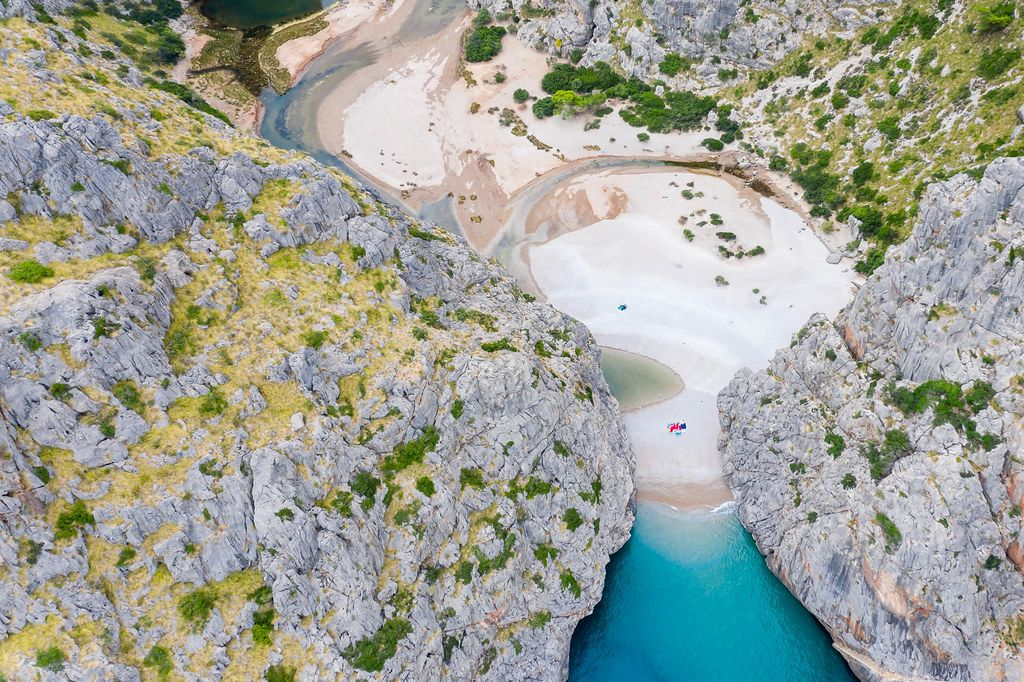 The estuary of the Torrent de Pareis forming the stunning bay of Sa Calobra in Mallorca. Aerial view