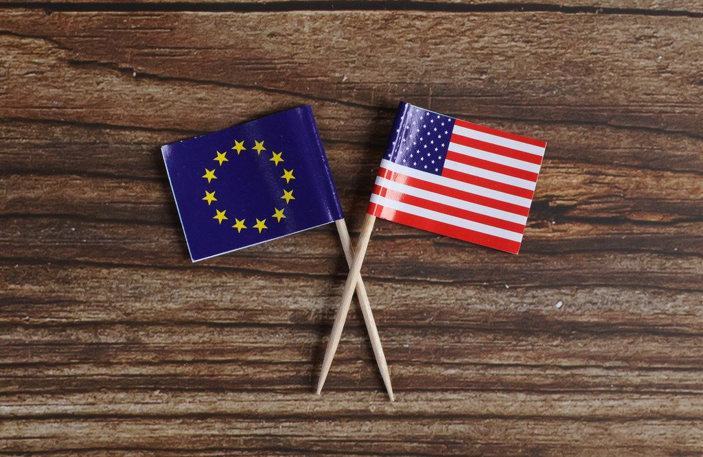 The European flag and American flag on wooden table