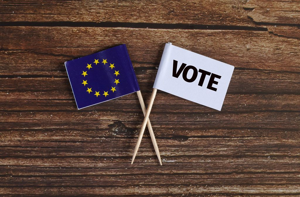 The European flag and white flag with vote text on wooden table