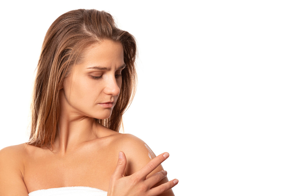 The girl applies a moisturizer to the skin of the shoulder