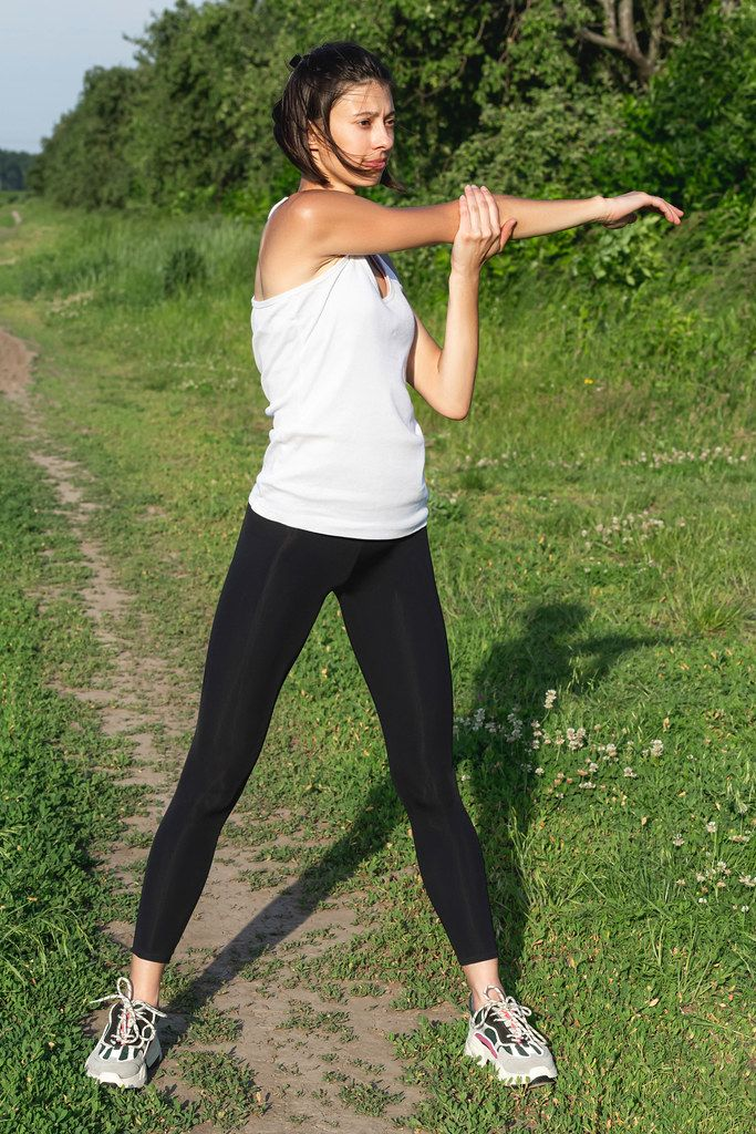 The girl is doing exercises in nature. Sports lifestyle