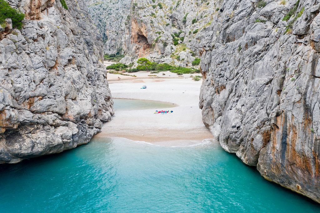 The hidden beach of Sa Calobra: turquoise waters between steep cliffs. Drone photo in Mallorca