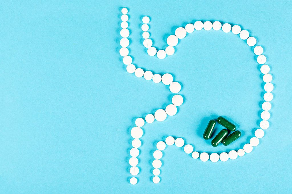 The human stomach of tablets on blue with green capsules