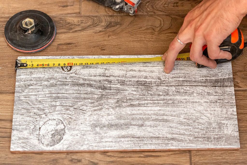 The master uses a tape measure to measure the dimensions on the tile