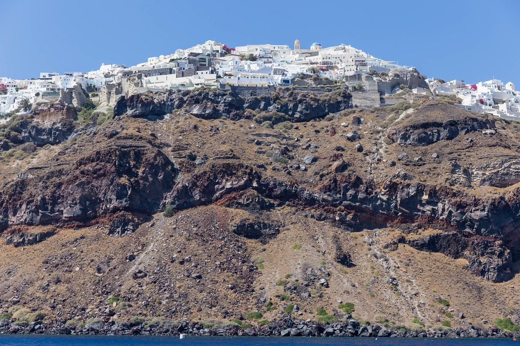 The picturesque village of Oia sits on layers of volcanic ground, seen from the sea during a boat trip