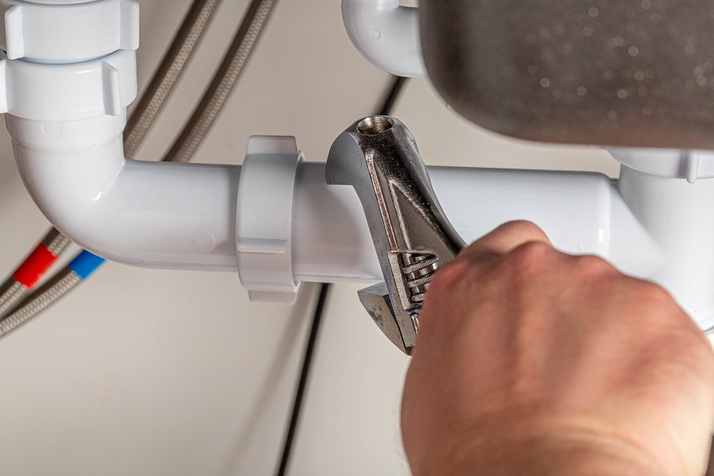 The plumber makes measurements of the diameter of the pipe using an adjustable wrench, close-up