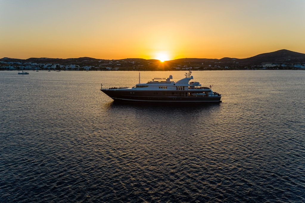 The sunset at the port of Adámas, Milos, Greece. The sea, a yacht and the sun setting behind the island