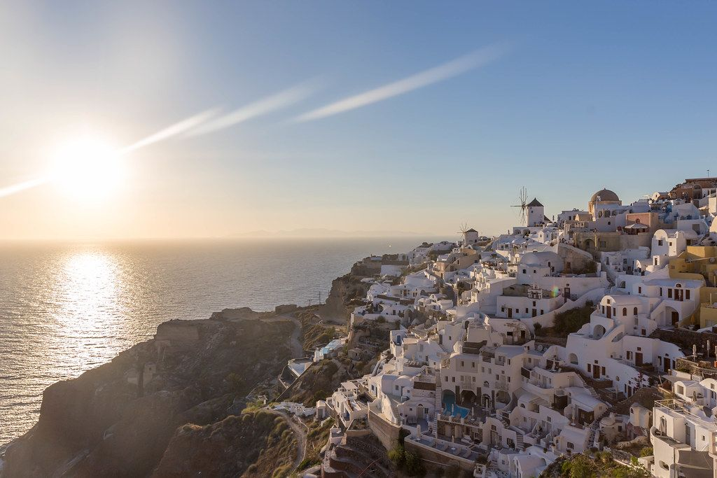 The sunset on the Aegean Sea and the picturesque village of Oia on the Greek island of Santorini