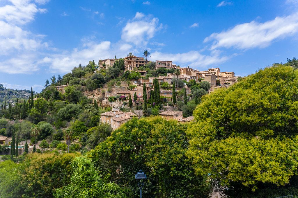 The village of Deià, Majorca, Balearic islands. Houses on a hill among trees with blue sky