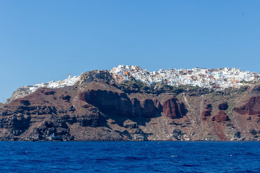 The volcanic cliffs of Santorini with the Aegean sea and the white village of Oia seen from a boat