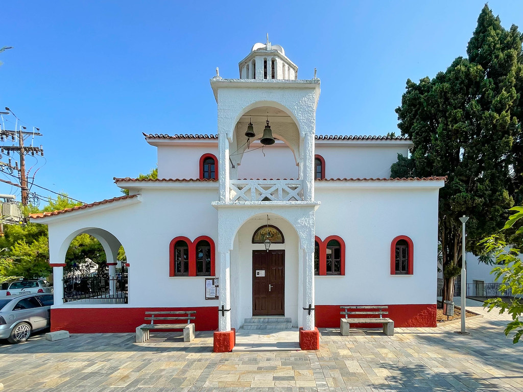 The white and red church of Agia Triada with central bell tower in Skiathos town, Greece