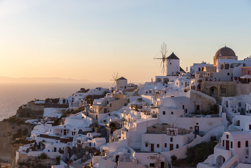 The white houses and windmills of Oia, Santorini, in the sunset light