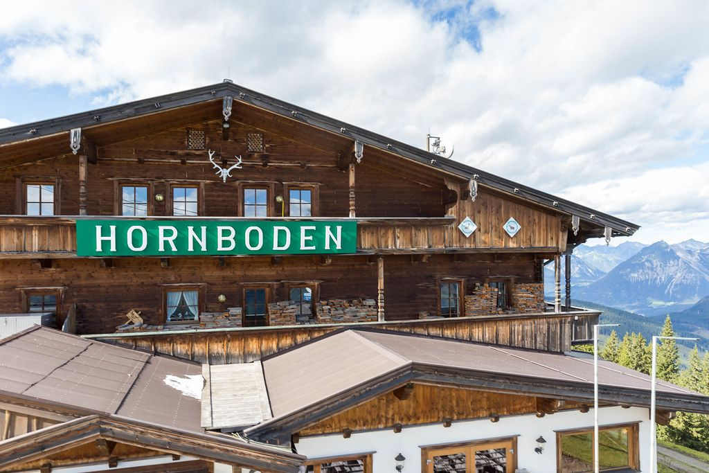 The wooden building of mountain restaurant Hornboden with its green sign and horns as a symbol