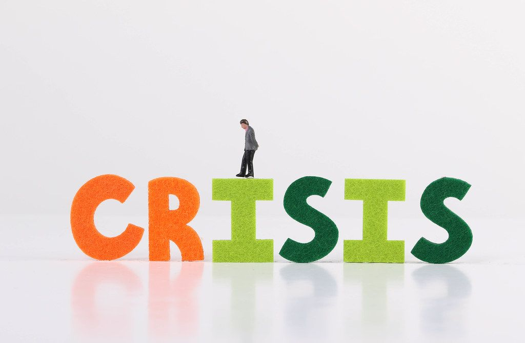 The word Crisis with businessman on white background