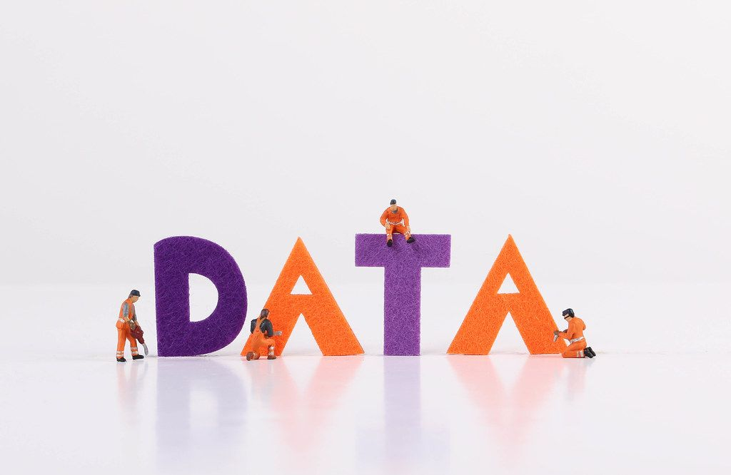 The word Data with tiny workers on white background