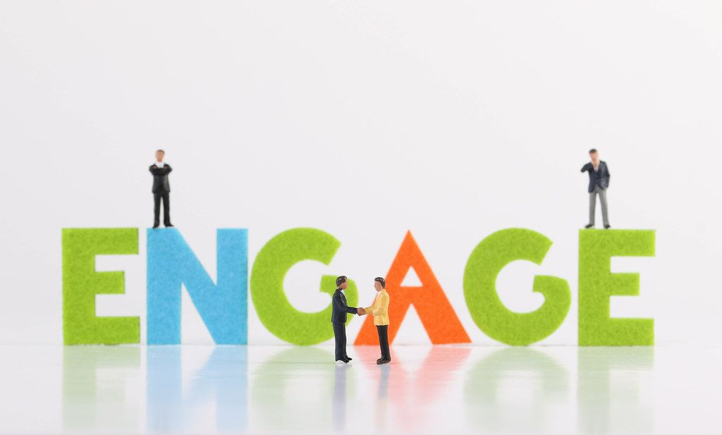 The word Engage with group of businessman on white background