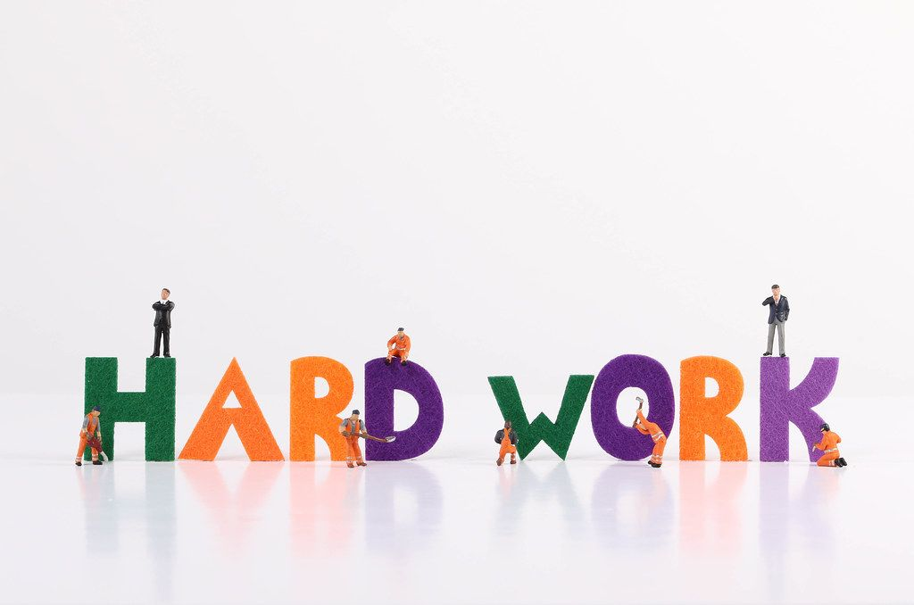 The word Hard Work with tiny workers on white background