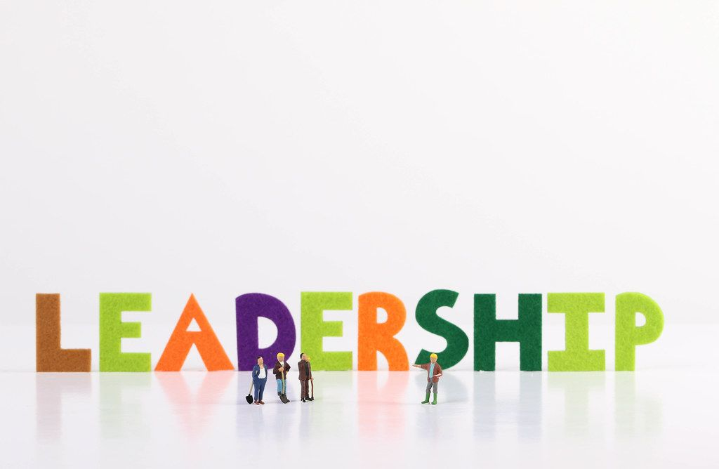 The word Leadership with construction workers on white background